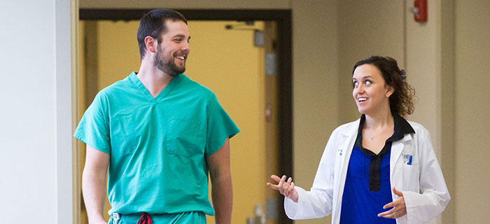 Two medical professionals walking and talking in hallway